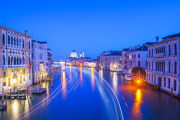 Light Trails On A Canal At Dusk With The Illuminated Salute Church In The Distance, Venice, Veneto, Italy