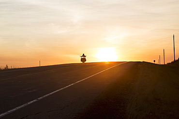 Man On A Motorcycle At Twilight On A Highway, Near Edmonton, Alberta, Canada