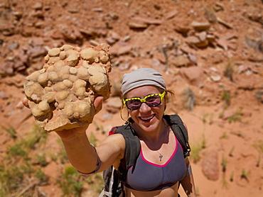 Female Adventurer With A Desert Rock Sample, Hanksville, Utah, United States Of America