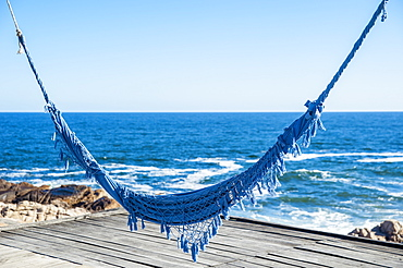 Blue Hammock Over A Wooden Dock At The Water's Edge, Cabo Polonio, Uruguay