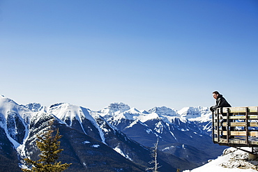A Man Stands With A View From Sulphur Mountain Of The Canadian Rockies In Winter, Banff, Alberta, Canada