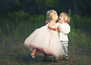 A Young Girl With A Pink Princess Dress Leans In To Kiss A Young Boy, Tarifa, Cadiz, Andalusia, Spain