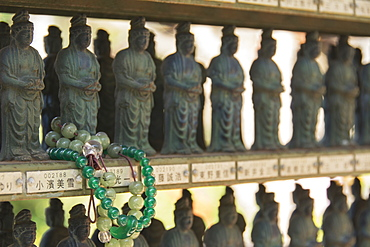 Buddhist Bracelet Wrapped Around A Temple Figurine Among Many, Ohara, Kyoto, Japan