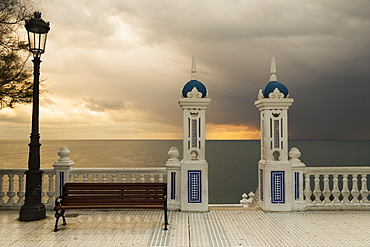 Decorative Railing And Pillars On The Promenade With A Bench And Lamppost At Sunset, Benidorm, Spain