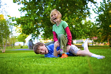 A Boy And Girl Wrestling On The Grass, Picton, Ontario, Canada