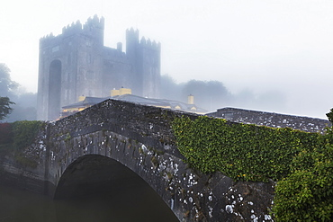 Old Stone Bridge With Castle In The Background And Fog, Bunratty, County Clare, Ireland