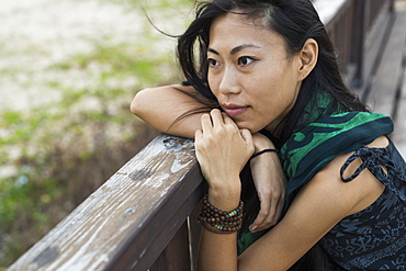 A Young Woman Sits Against A Wooden Railing Looking Out At The Ocean, Jincheng, Kinmen, Taiwan