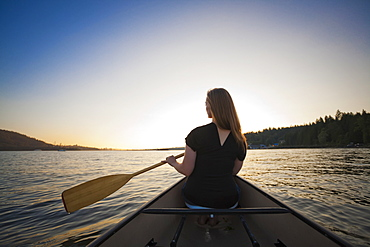 A Young Woman Canoeing At Sunset, Vancouver, British Columbia, Canada