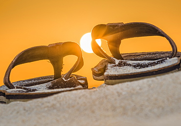 Brown Leather Sandals On The Sand With A Glowing Orange Sky And Sun, Spain