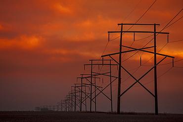 Power Lines At Sunset With Glowing Orange Sky, Saskatchewan, Canada