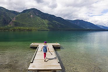 Young Girl On A Dock At Muncho Lake Provincial Park, British Columbia, Canada, Summer