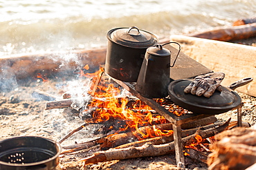 Close Up Of Coffee Pot And Cast Iron Dishes Over A Campfire, Yukon Territory, Canada