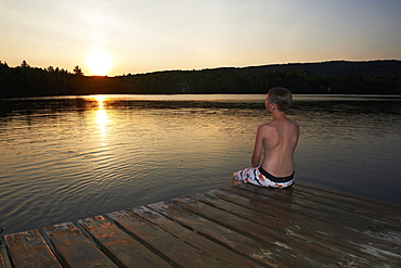 Boy Sitting On The Dock With Feet In Water At Sunset, Lac Des Neiges, Quebec, Canada