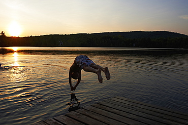 Boy Diving Into A Lake At Sunset, Lac Des Neiges, Quebec, Canada
