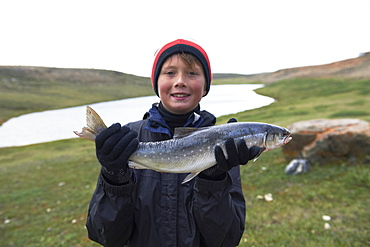 Boy Holds Fresh Caught Arctic Char Near Cambridge Bay, Nunavut, Canada