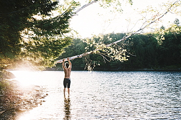 A Young Man Stands At The Edge Of A Lake Holding On To A Leaning Tree, Waterbury, Vermont, United States Of America