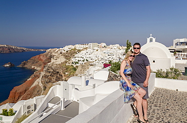 A Couple Posing Together On A White Wall On A Greek Island With The Town In The Background, Santorini, Greece