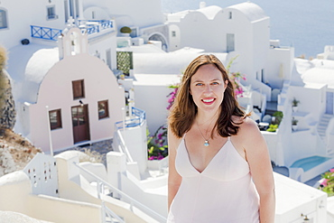 A Woman Poses With Whitewash Church And Buildings In The Background, Santorini, Greece