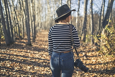 Young Woman Wearing Hat With Camera And Walking Through The Woods Near Creamer's Field, Fairbanks, Interior Alaska, Autumn
