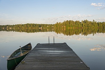 Canoe Beside A Wooden Dock On A Tranquil Lake, Ontario, Canada