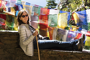 A Woman Rests On A Wall Beside Colourful Prayer Flags, Paro, Bhutan