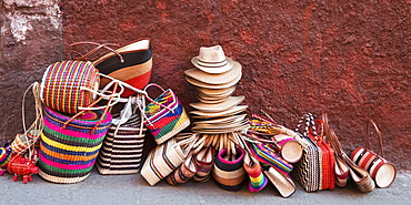 Woven Souvenirs On Display On A Sidewalk Against A Wall, San Miguel De Allende, Guanajuato, Mexico