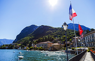 Sunshine On The Italian Flag And Waterfront Views From The Town Of Menaggio On Lake Como, Menaggio, Lombardy, Italy