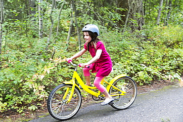 A Young Girl Rides Her Yellow Bicycle On A Trail, Salmon Arm, British Columbia, Canada