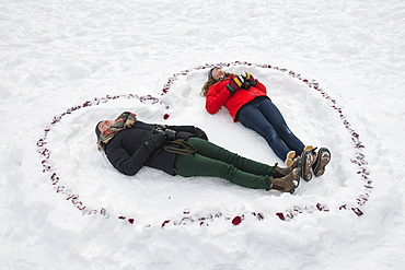 Two Young Women Laying In The Snow Inside A Heart Shape, Alberta, Canada