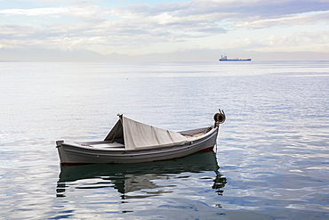 A Boat Floating On The Tranquil Aegean Sea With A Ship In The Distance, Thessaloniki, Greece