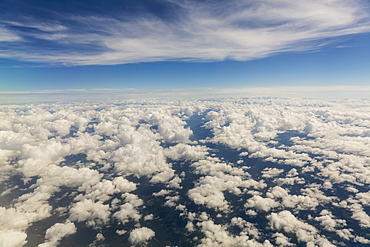 Aerial View Of Scattered Clouds, Snow Covered Peaks Rising Above The Clouds In The Background, Alaska, United States Of America