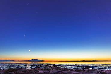 The Moon Rises Above Mount Susitna On A Clear Winter Night, Sea Ice Visible In The Foreground, Anchorage, Alaska, United States Of America