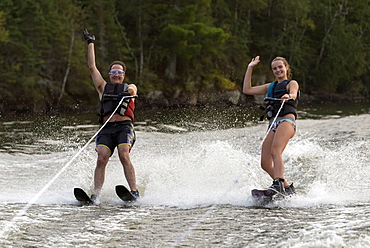 A Father And Daughter Waterskiing Side By Side While Waving To The Camera, Ontario, Canada