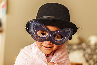 Young Girl Playing Dress Up Wearing A Mask And Hat, Edmonton, Alberta, Canada