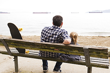 A Father And His Little Girl Sit On A Bench And Watch The Ships Anchored In The Sea, Vancouver, British Columbia, Canada