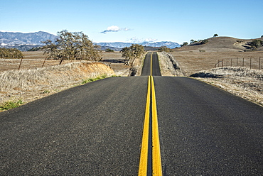 A Hilly Road With Double Solid Yellow Lines Leading Into The Distance In A Rural Area, Near Santa Ynez, California, United States Of America