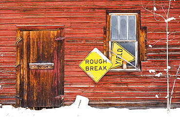 A Red Wooden Building With Two Yellow Signs, Saying 'rough Break' And 'yield', Wetaskiwin, Alberta, Canada