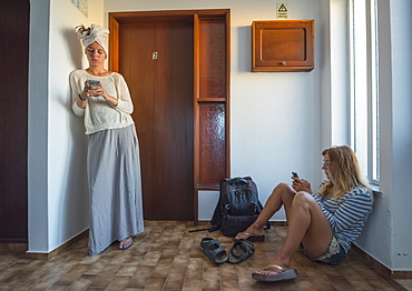 Two Young Women In Their Apartment Using Their Smart Phones, Sagres, Portugal