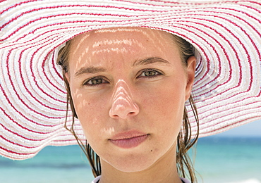 Portrait Of A Young Woman Wearing A Red And White Striped Sunhat, Tarifa, Cadiz, Andalusia, Spain