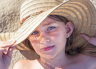 A Girl Laying On The Sand Wearing A Sunhat, Tarifa, Cadiz, Andalusia, Spain