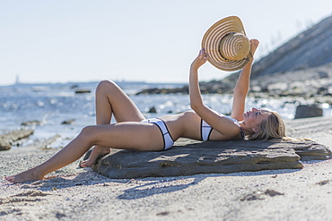 A Young Woman In A Bikini Lays On A Piece Of Driftwood On The Beach Holding A Sunhat Up To Shield The Sun, Tarifa, Cadiz, Andalusia, Spain