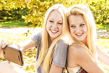 Two Sisters Having Fun Outdoors In A City Park In Autumn And Taking A Selfie, Edmonton, Alberta, Canada