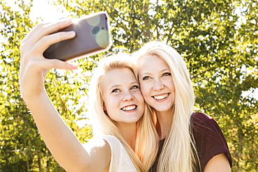 Two Sisters Having Fun Outdoors In A City Park In Autumn And Taking Selfies Of Themselves, Edmonton, Alberta, Canada
