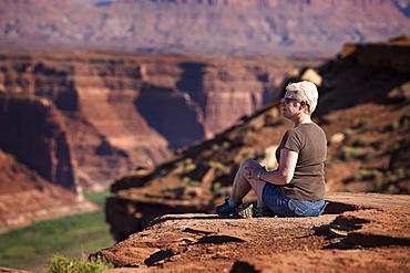 Woman Sitting On The Edge Of A Rock Canyon Cliff Looking Over The Colorado River With Canyon Walls In The Background, Colorado, United States Of America