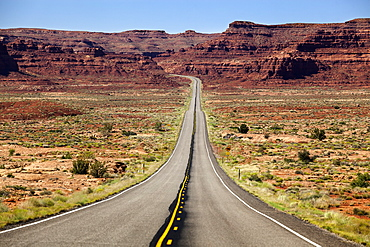Utah Highway Stretching Into The Distance With Rock Cliffs And Blue Skies In The Background And Desert Vegetation On Either Side Of The Road, Utah, United States Of America