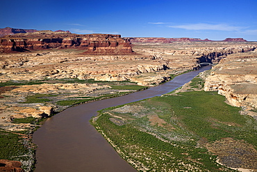 Low Altitude Aerial View Of The Colorado River Winding Through Canyon Country Of Southern Utah, A Bridge Spanning The River In The Background With Red Rock Canyon Walls And Blue Skies, Utah, United States Of America