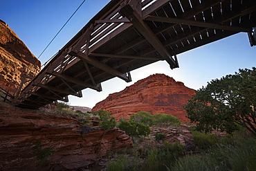 A Footbridge Spanning A Canyon Stream Stretches Overhead With Tall, Red-Rock, Canyon Walls In The Background, Viewed From Under The Bridge, Utah, United States Of America