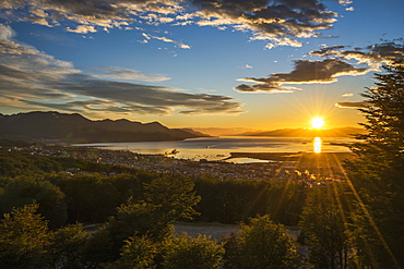 The Sun Rises Over The Port Of Ushuaia In Argentina As A Ship Enters The Calm Bay, Trees In The Foreground And Low Hills On The Horizon, While The Sky Is Dotted With Clouds And Turns From A Golden Yellow To A Deep Blue, Ushuaia, Argentina
