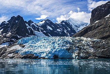 Blue Glacier Between Snow-Capped Mountains And Fjord, Antarctica