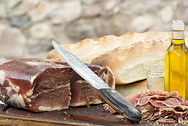 An Outdoor Scene Of A Knife Is Resting On Top Of A Block Of Prosciutto With Bread And Olive Oil, Mendoza, Argentina